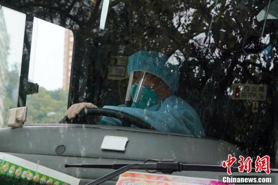 防護服を着用して「ダイヤモンド・プリンセス」号の乗客を乗せたバスを運転する運転手(撮影・張煒)。