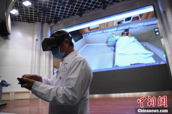 VR機器を利用して病室を回診する医師 (撮影・康平)。