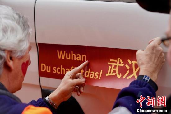 24日午後、ドイツ・ミュンスター市で行われた「バラの月曜日」のパレードで、先頭を務める「1号」山車の両側に貼られた「武漢必勝」のスローガン(撮影・彭大偉)。
