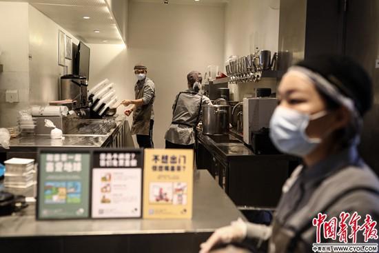 2月22日、湖北省武漢市楚河漢街にあるミルクティー店で、最前線で奮闘する医療スタッフに送り届けるためにミルクティーを作る24歳の店員の陳世昌さん(写真左、撮影・趙迪)。