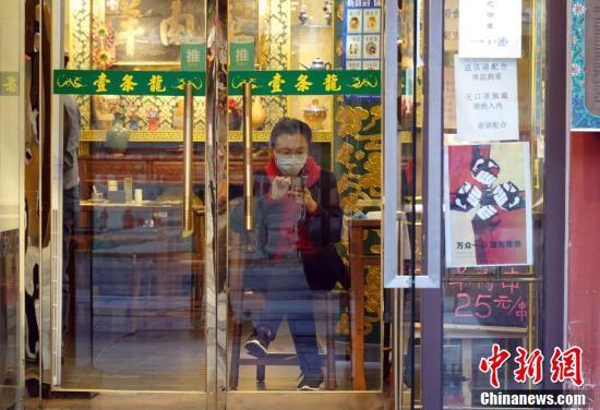 3月7日、北京のあるレストランの入り口で客の来店を待つ店員(撮影・毛建軍)。