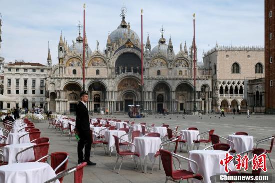 ヴェネツィアのサン・マルコ広場で、誰も座る人のいないテーブル席の傍にたたずむウェイター。