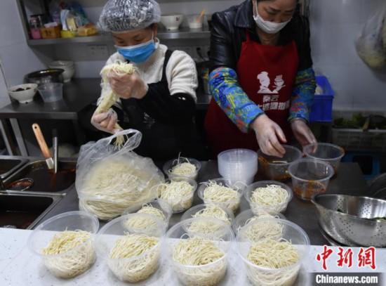 「重慶小麺の未調理食材セット」の配達準備をする重慶のあるレストランのスタッフ(撮影・周毅)。