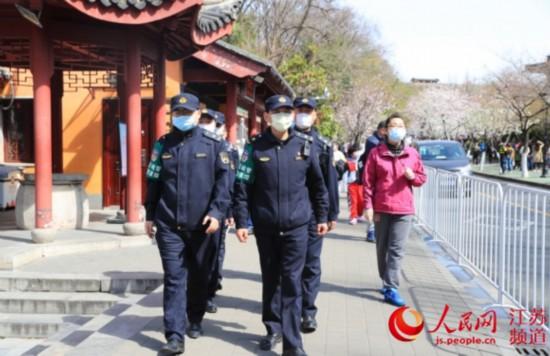 图为樱花绽放期间,玄武城管队员在鸡鸣寺路巡逻。玄武区城管局供图