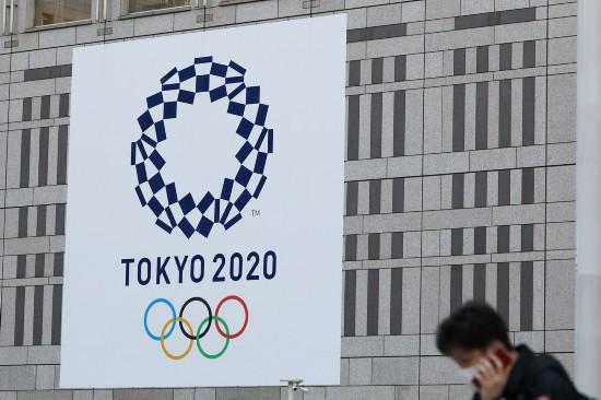行人经过日本东京都厅前的东京奥运会会徽 (2020年3月25日摄)。