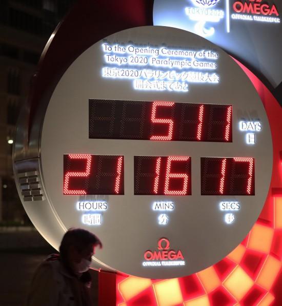 3月30日,行人经过日本东京站前显示东京残奥会开幕式倒计时的电子钟,电子钟已根据新宣布的开幕时间进行调整。