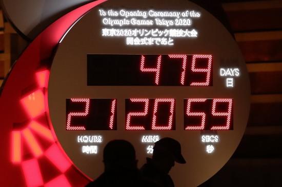 3月30日,行人经过日本东京站前显示东京奥运会开幕式倒计时的电子钟,电子钟已根据新宣布的开幕时间进行调整。