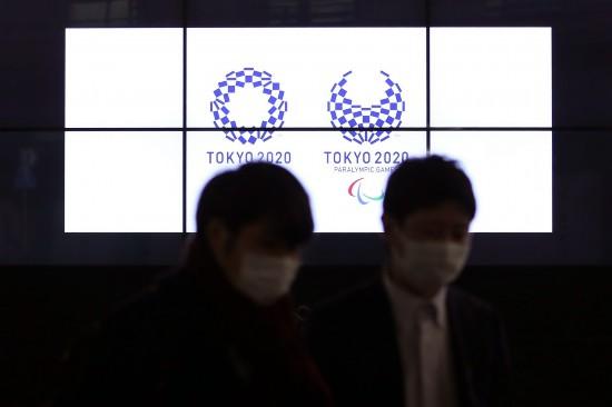 3月30日,在日本东京新桥,行人经过显示东京奥运会和残奥会会徽的电子屏。