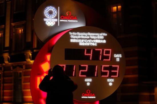 3月30日,行人在日本东京站前拍摄显示东京奥运会开幕式倒计时的电子钟,电子钟已根据新宣布的开幕时间进行调整。