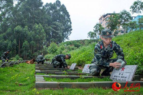 4月3日,武警廣西總隊機動支隊軍犬班的馴導員們在打掃軍犬墓園。