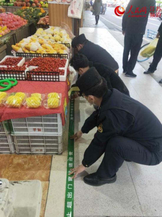 """4月7日,六合区城管执法大队执法队员与福广街沿线的店家们在店门口贴上""""门前三包警戒线""""。六合区城管局供图"""