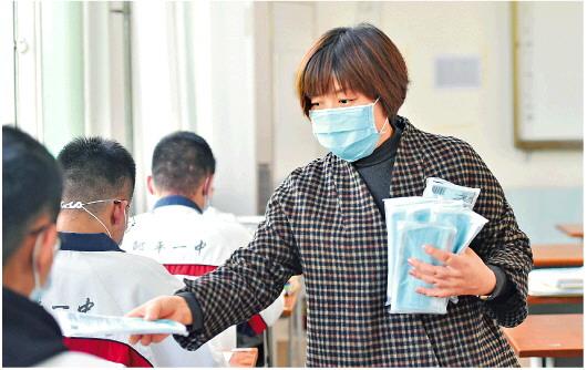 4月14日,邹平市第一中学教师在为学生分发口罩。(□新华社发)