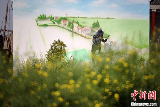 壁に美しい郷村の景色を描く画家(撮影・泱波)。