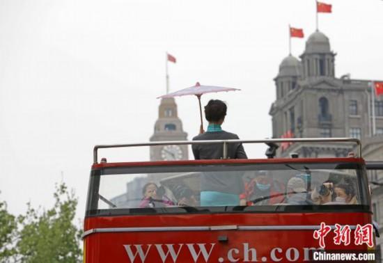 「都市観光」オープントップバスの2階で、春秋航空の「春の翼」チャイナドレスCAチームを撮影する写真愛好家(撮影・殷立勤)。