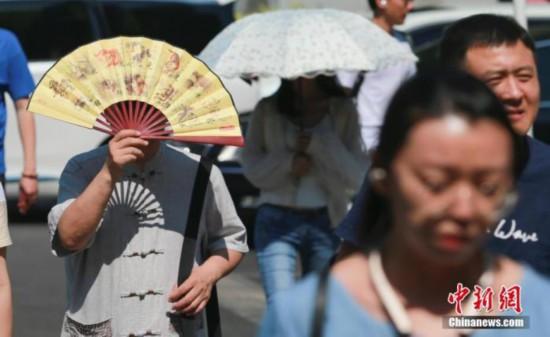 北京の街を日差しを遮りながら歩く人々(資料写真、撮影・賈天勇)。