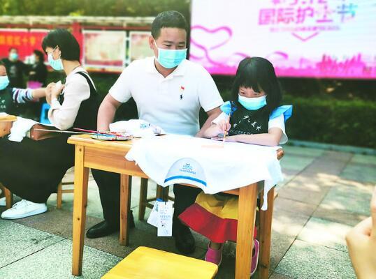 王彬彬与孩子一起手绘T恤。
