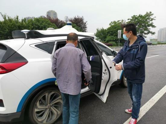 长沙梅溪湖国际文化艺术中心附近,一位市民在随车安全员引导下,准备登车试乘百度阿波罗自动驾驶出租车。新华社记者刘良恒 摄