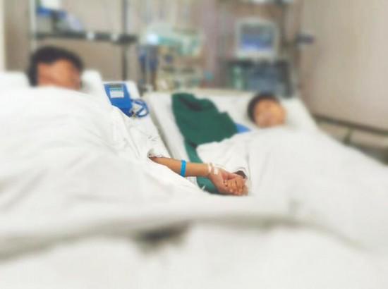 父子俩在重症病房里手拉手。