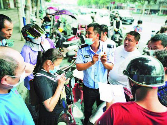 执勤辅警在给市民介绍如何填写申请表。