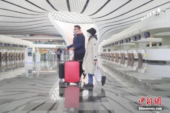 1月26日、新型コロナウイルス感染状況の影響を受け、マスクを着用して北京大興国際空港内を歩く男女。(撮影:賈天勇)