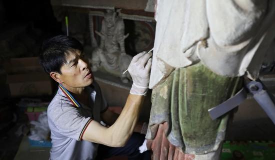 6月8日,工作人員對奉國寺的彩繪泥塑進行保護修復。