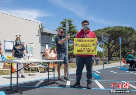 米国現地時間5月15日、カリフォルニア州サンマテオ郡の高校で、卒業生がすべて非接触で卒業記念品の受け取りなどの手続きを行う様子(資料写真・劉関関)。