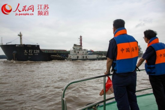 图为长江镇江段,海事部门护航大型船舶经过裕隆洲口。