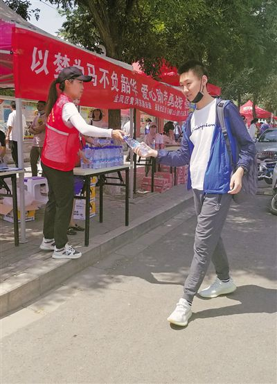 <p>    在银川六中考点,金凤区黄河东路街道办事处在考点外设立志愿服务点,为考生赠送矿泉水。本报记者 陶涛 摄 </p>