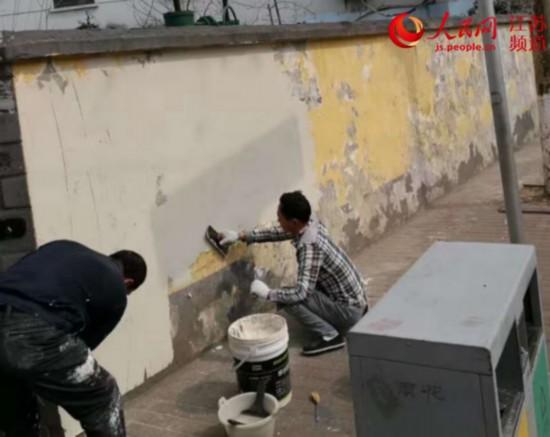 資料圖片:工人正進行新型防張貼材料噴涂。雨花台區城管局供圖