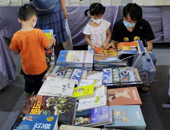 """家长带着孩子在北京少年儿童出版社""""冰心奖""""专台挑选"""