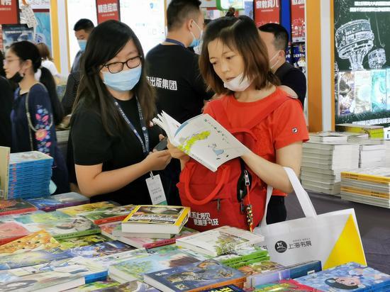 读者在北京出版集团展位翻阅图书