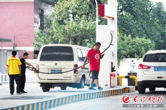 一名加油的顾客在加油岛作业区长时间使用手机,但一旁的加油员并未进行劝阻。长沙晚报全媒体记者 刘琦 摄
