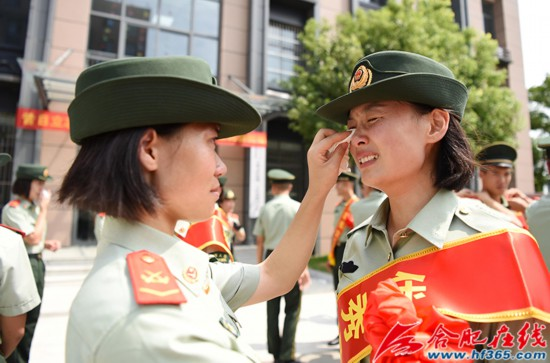 圖20:2020年8月31日,安徽合肥,在武警合肥支隊執勤四中隊向警徽告別儀式上,一名女兵在給退伍女兵擦拭淚水。