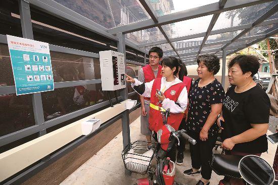 7月31日,中央門街道新門口社區志願者向居民介紹智能充電樁的使用方法。