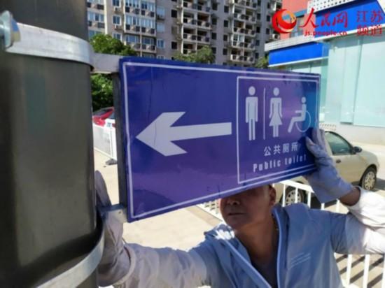 圖為工人正在新安裝公廁位置指示牌。玄武城管供圖