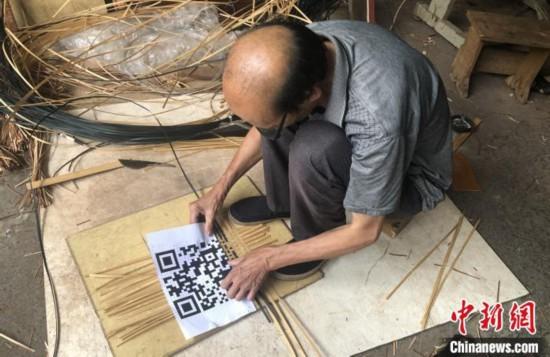 谢世仰将竹篾有序地摆在地上,对照着打印出来的二维码开始编织。 彭莉芳 摄