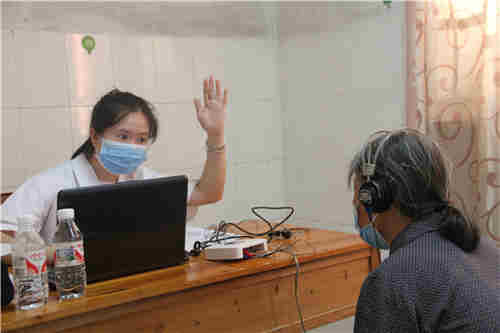 图为自治区听力言语康复中心听力师邱美珍为贫困疑似残疾人进行外耳道检查