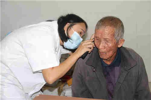 图为自治区听力言语康复中心听力师向尧云在坛洛镇卫生院为贫困疑似残疾人进行免费评残