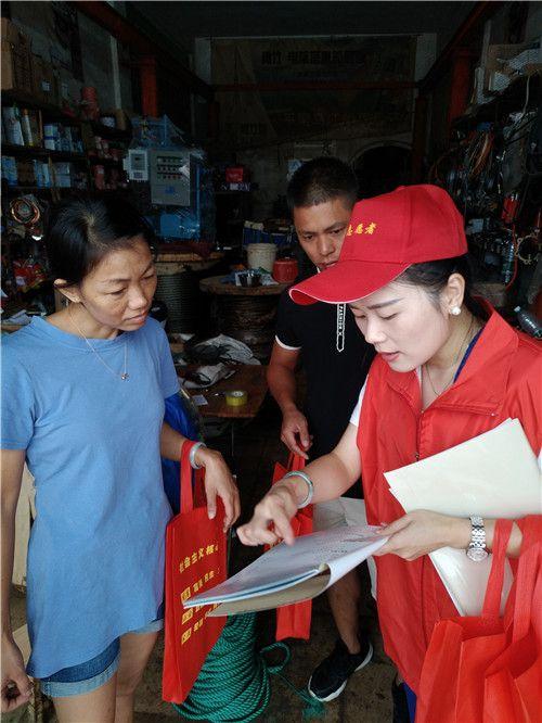 图为志愿者入户向居民宣传惠残政策、文明城市创建