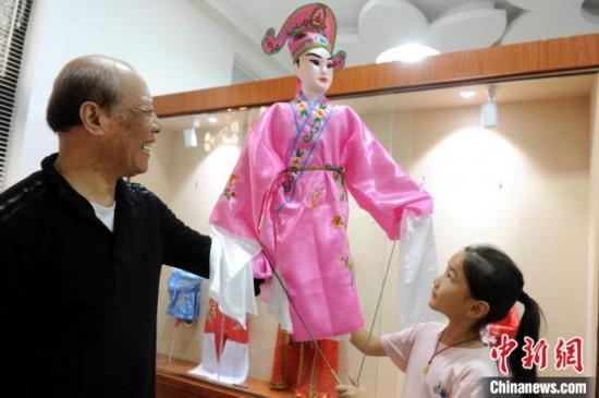 杨亚州展示他的木偶作品。 张金川 摄