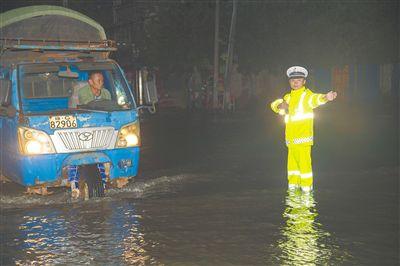 万宁交警在积水的路上坚守岗位指挥交通