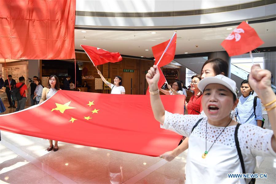 Participants chorus Chinese national anthem during flash mob in Hong Kong