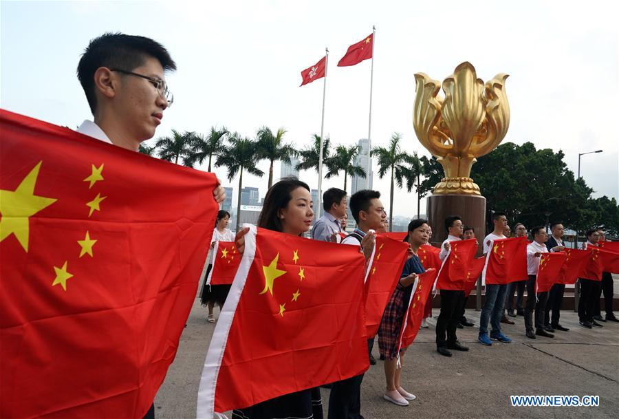 Young people hold up China's national flag during flash mob in Hong Kong
