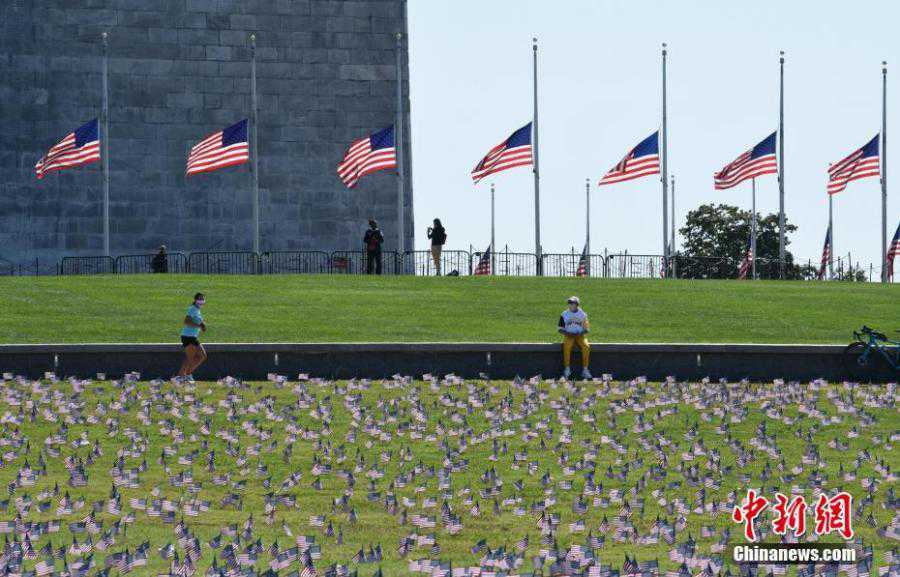 Thousands of flags cover the National Mall to memorialize COVID-19 deaths