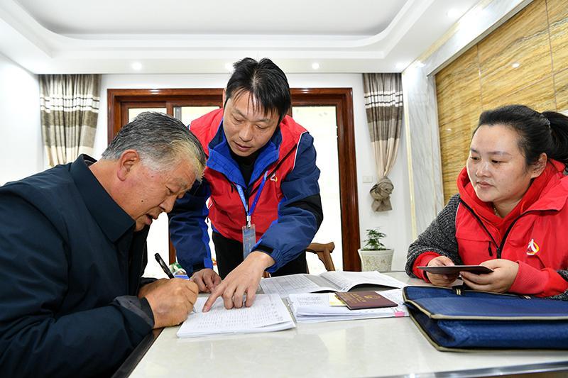 11月1日,湖北省襄阳市保康县城关镇普查员、普查指导员在居民家中进行信息登记后,居民核实后签字确认。新华社发(杨韬 摄)