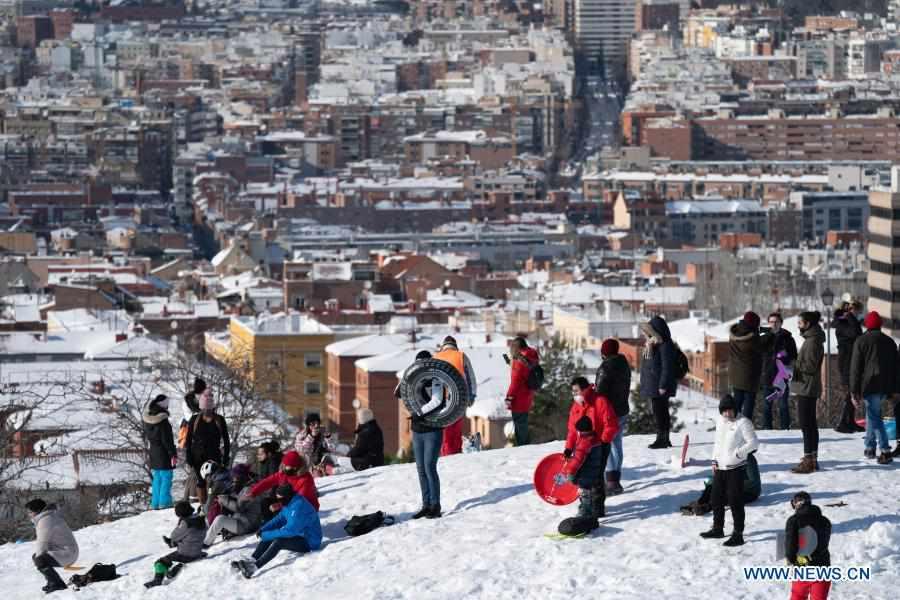 People enjoy snow in park in Madrid, Spain