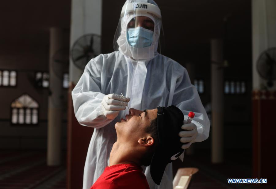 Medical workers collect swab samples from people in southern Gaza Strip city of Rafah Strip city of Rafah