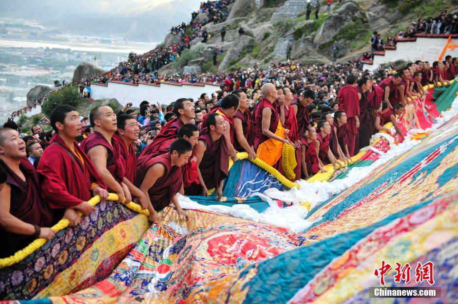 8月25日,拉萨哲蚌寺举行展佛仪式,僧人们协力展开巨幅释迦牟尼佛像。