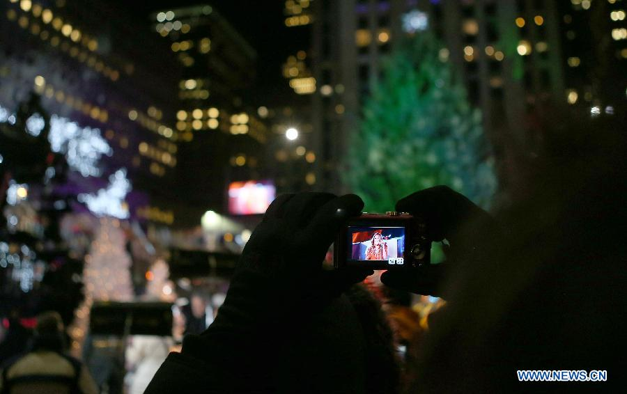 A visitor takes photos of American singer Mariah Carey's performance in front of the Christmas tree during the 82nd Christmas Tree Lighting Ceremony in Rockefeller Center in New York, the United States, Dec. 3, 2014.