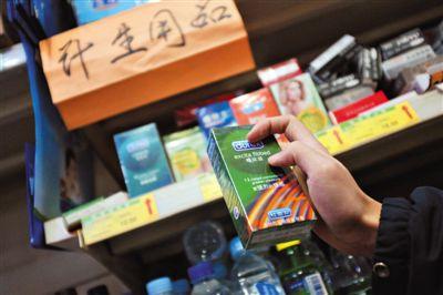 """清苑路""""世纪华联超市清友园店""""的货架上,摆放着购自网店的""""高仿""""避孕套。新京报记者"""
